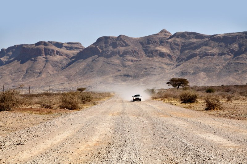 A car drives along a dirt or gravel road in the dry, arid, rural landscape of Namibia