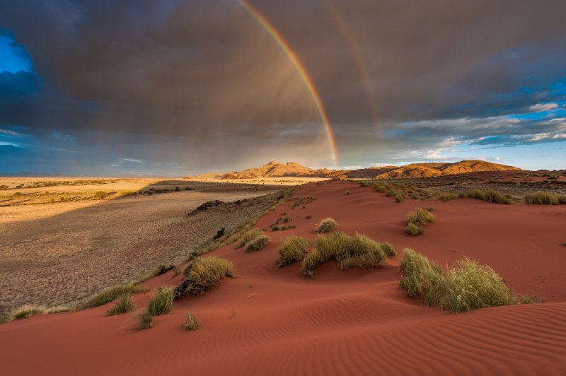 A horizontal landscape photograph of a rainbow across the Namibian Desert and mountains during a passing storm in the afternoon in Namib Rand, Namibia