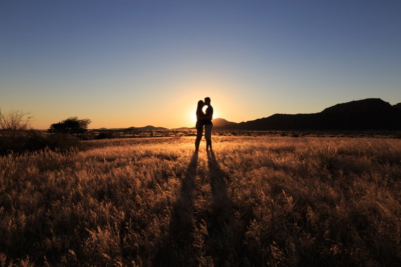 Couple kissing at african savanna landscape. Namibia, South of Africa
