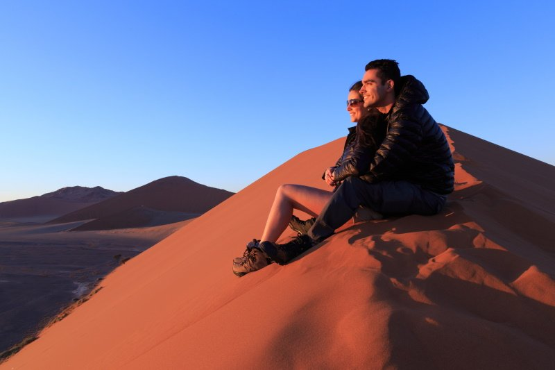 Couple on sand dune in desert during sunrise. Sossusvlei, Namib Naukluft National Park, Namibia