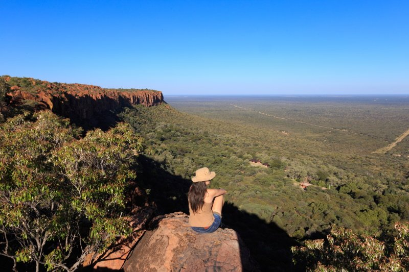 Girl sitting on stone on the cliff at an african landscape. Waterberg plateau, Namibia. Relax time on holiday concept travel