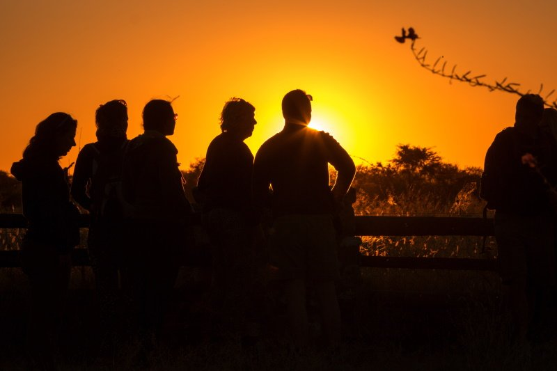 Group of people enjoying a amazing sunset in northern Namibia, Etosha National Park. Africa