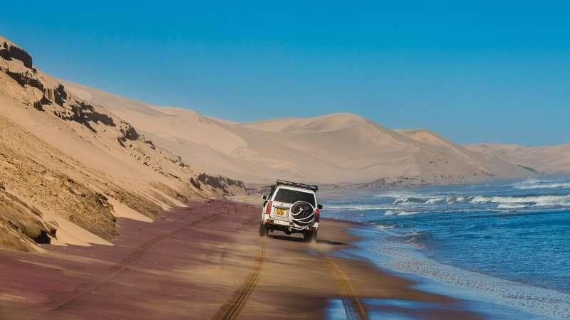 Namib desert at Walvis bay, Namibia, June 15, 2017 adventure drive with a Nissan Patrol offroad car at the sand dunes of the Namib desert at Walvis bay reaching the Atlantic ocean