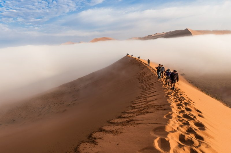 SOSSUSVLEI, NAMIBIA - CIRCA AUGUST 2015 - Tourists climb up the Dune 45 through the early morning fog in Sossusvlei, Namibia
