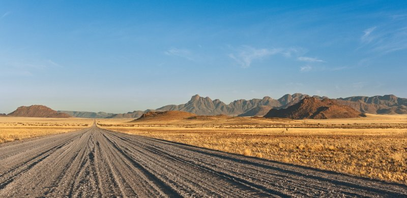 gravel road passing through the steppe and mountains in the background, Africa Namibia