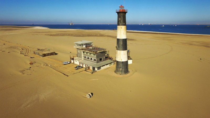 old lighthouse, old power station building on seals beach, Walvis Bay lagoon with sea ships at Namibia's Atlantic west coast, southern Africa